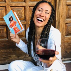 Elaine Welteroth holding More Than Enough and glass of wine