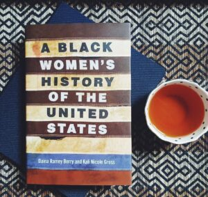 Nonfiction book: A Black Women's History of the United States next to a cup of tea