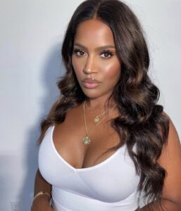 Picture of MakeupShayla in white shirt and long waves with a summer glow makeup look