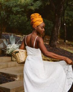 Woman in a white dress holding a basket of flowers with a yello headwrap against a nature backdrop